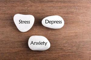 palavra de estresse, depressão e ansiedade de pedras brancas foto