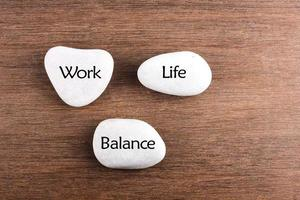 palavra de equilíbrio de trabalho e vida de pedras brancas sobre fundo de madeira foto