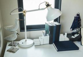 mesa de trabalho com lâmpada, lápis, livros em uma casa foto