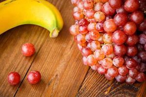 uva vermelha com banana na mesa de madeira foto