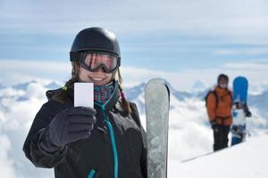 menina segurando o bilhete de esqui em branco sorrindo