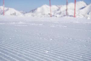 trilhas de groomer neve fresca em uma pista de esqui foto