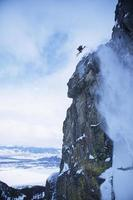 esquiador pulando do penhasco da montanha foto