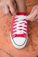 mulher amarrando os sapatos antes de correr no parque foto