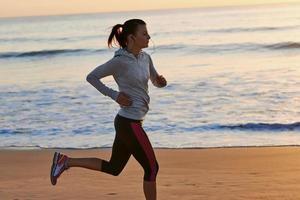 mulher de aptidão correndo na praia foto