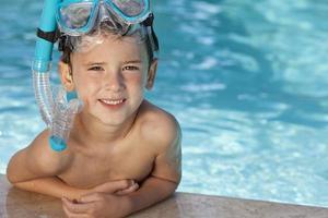 garoto feliz na piscina com óculos azuis e snorkel foto