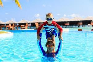 pai e filho se divertindo na piscina foto