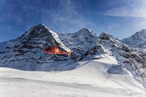 pouso de helicóptero vermelho na estância de esqui suíça perto de jungfrau mountai