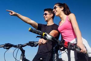 casal jovem feliz em um passeio de bicicleta na zona rural foto