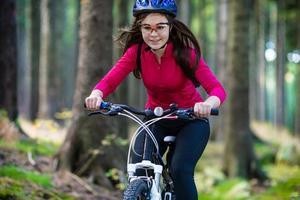menina andando de bicicleta em trilhas da floresta foto