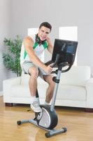 sorridente homem bonito treinando na bicicleta ergométrica usando laptop foto