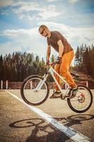 homem pular de bicicleta pela linha branca foto