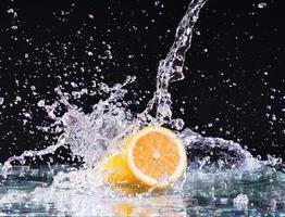 respingos de água macro no limão. gotas de água com limão suculento foto