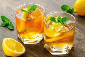 chá gelado de limão na mesa de madeira marrom com limões ao redor foto