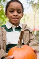 garoto segurando uma abóbora foto