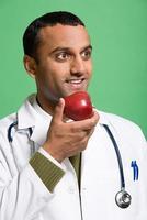 médico comendo uma maçã foto