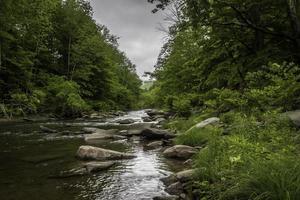 riacho rochoso em movimento sob o céu dramático