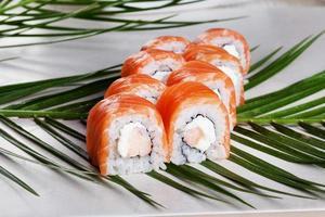 Filadélfia roll com comida de sushi de camarão em uma palmeira tropical