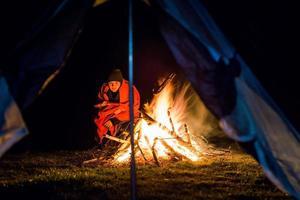 jovem perto da fogueira de acampamento com cobertor foto