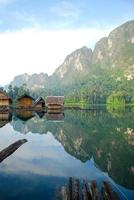 cabana à beira do lago tropical e barco de madeira