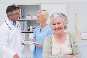 paciente sorrindo enquanto médico e enfermeira discutindo em segundo plano