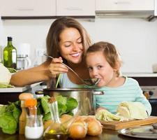 mãe feliz com a filha cozinhando juntos