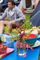 mesa de decoração de flores silvestres em férias de acampamento em família foto