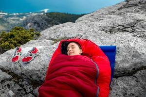 mulher em saco de dormir na montanha foto
