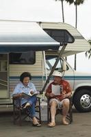 casal relaxando fora de seu rv foto