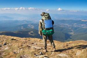 alpinista masculina fica em um pico de montanhas foto