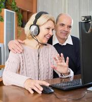 pensionista sentados juntos no computador foto