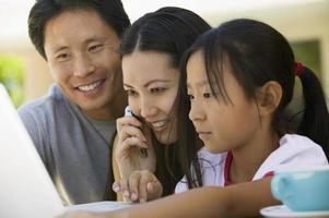 família com telefone celular e laptop foto
