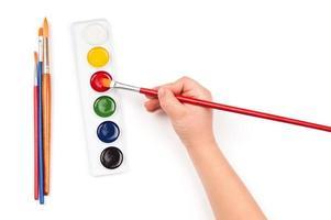 a mão da criança mergulha o pincel em aquarela