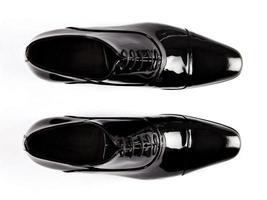 par de sapatos masculinos pretos sobre fundo branco foto