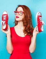garota de vestido vermelho com sapatos desportivos foto
