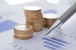 caneta com gráficos de linha e moedas na mesa foto