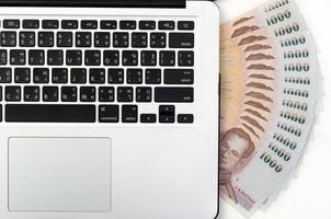 dinheiro e teclado de laptop foto