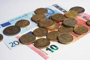 notas e moedas de euro espalhadas sobre uma superfície branca ii foto