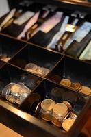 caixa registradora cheia de dinheiro foto