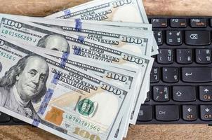 pilha de notas de cem dólares no teclado foto