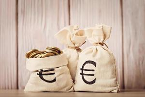 sacos de dinheiro com moedas de euro sobre fundo desfocado de madeira foto