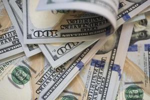 closeup de notas de US $ 100 enroladas e planas foto