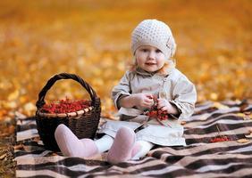 criança bonita e cesta com rowan berry vermelho no outono