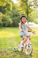 retrato de menina feliz, andar de bicicleta ao ar livre no parque foto