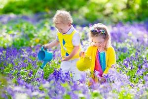 filhos adoráveis em um jardim com flores de bluebell
