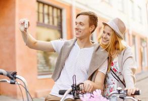 casal com bicicletas e câmera tirando foto de selfie