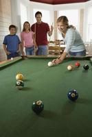 família jogando sinuca na sala de recreação foto