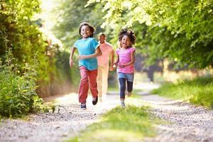 crianças correndo na zona rural com o pai