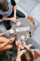 jovens amigos jogando poker jogo de cartas no café foto