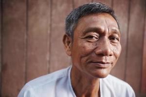 velho asiático, olhando para a câmera contra parede marrom foto